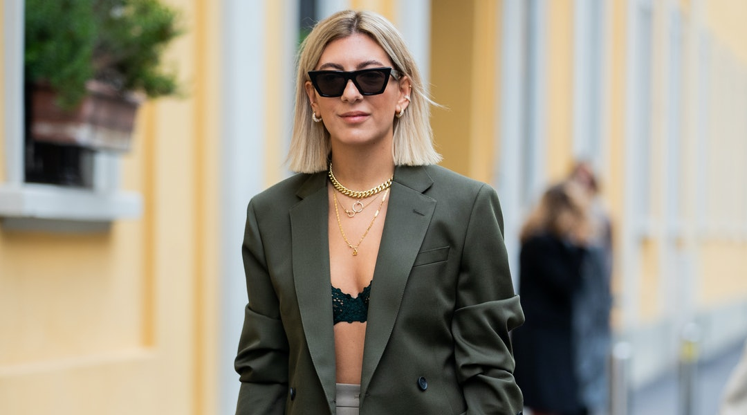 Aylin Koenig is seen weairng white Dior bag, midi skirt, bra, olive blazer outside Boss during Milan Fashion Week Spring/Summer 2020.