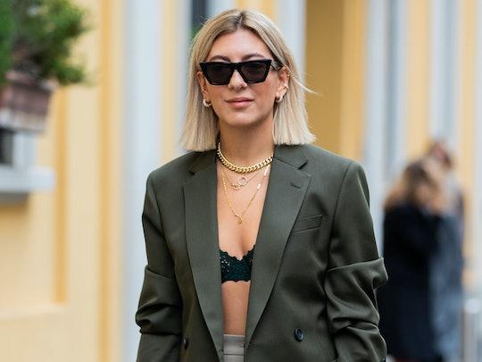 Aylin Koenig is seen weairng white Dior bag, midi skirt, bra, olive blazer outside Boss during Milan Fashion Week Spring/Summer 2020.