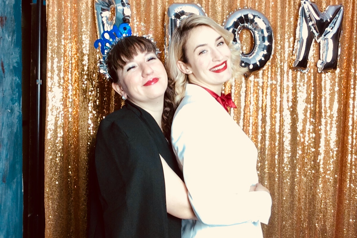 Two friends smile and pose for a New Year's Eve photo in a glittery photo booth.