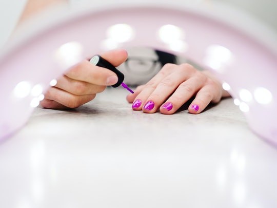 Hand paints the nails, gel purple, gel nail manicure through the lamp for manicure