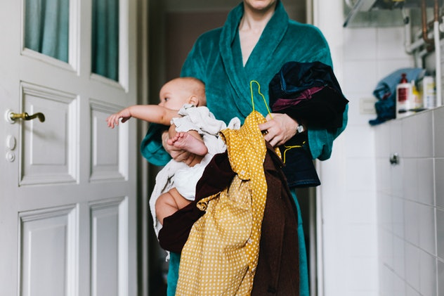 Woman carrying bundle of laundry and also a baby