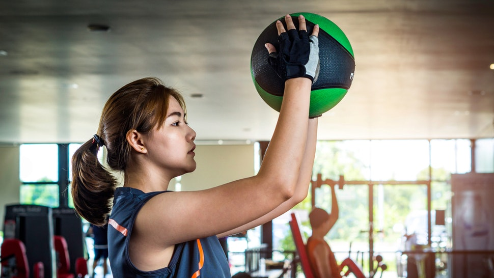 A person in a blue tank top and exercise gloves holds an exercise ball above her head, poised to slam it down. If your new year's resolution is to exercise but you haven't thought about your goals, you might want to ask yourself this workout question.
