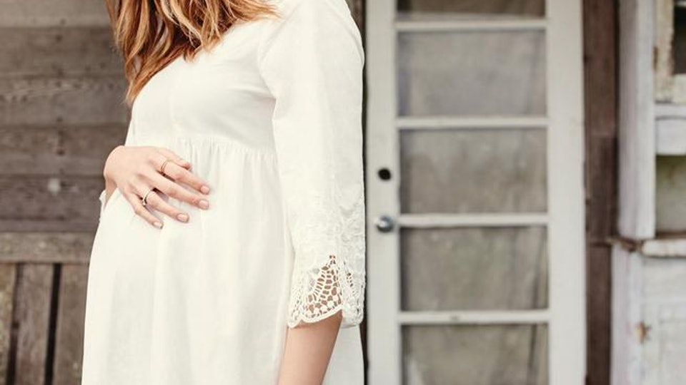 a pregnant woman wearing a dress from Ingrid & isabel