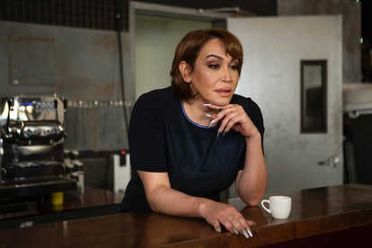 A transgender woman standing at a bar with her hand under her chin. Dry January is not the only dry month for many who are living in recovery.