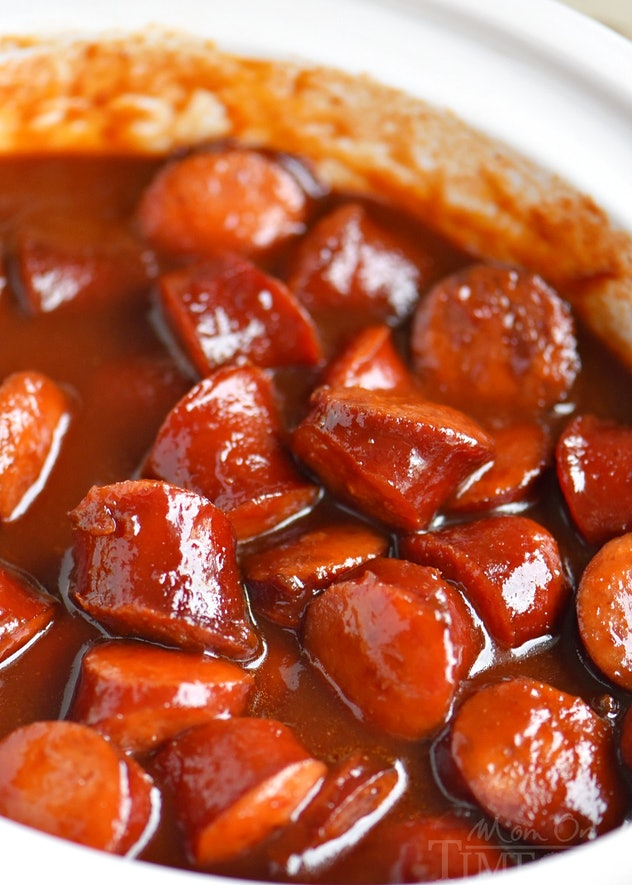 close up shot of glossy kielbasa cut up into bite-size pieces in sauce