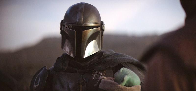 Pedro Pascal as Mando holding Baby Yoda in The Mandalorian