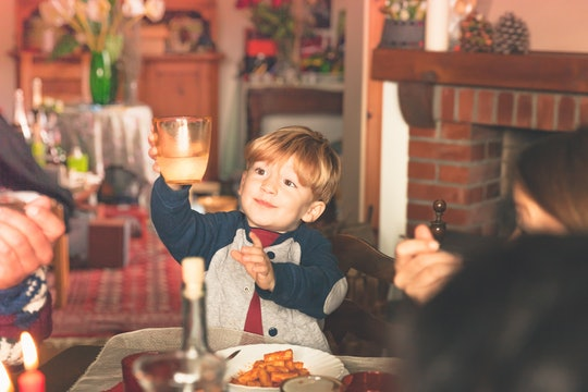 child raises glass to new year's eve