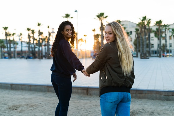 Two young women holding hands at sunset. Twin flame relationship
