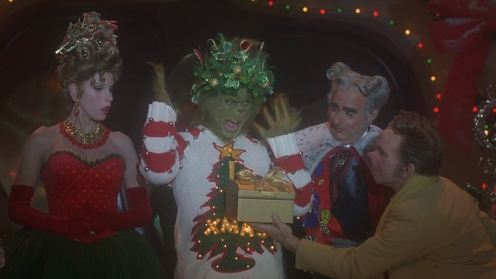 The Grinch from 'Dr. Seuss' How The Grinch Stole Christmas' wears a festive sweater and opens a present in the movie.