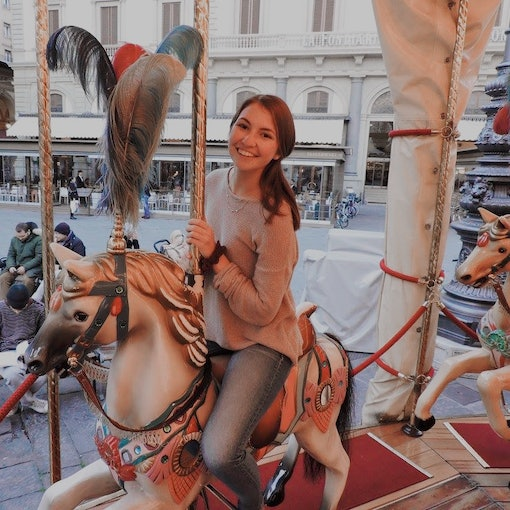 A girl wearing jeans and a sweater smiles on a carousel in Florence, Italy around the holidays.
