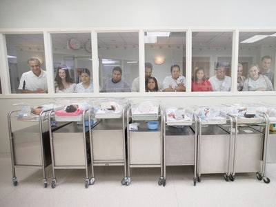 parents peer in at babies in a hospital nursery