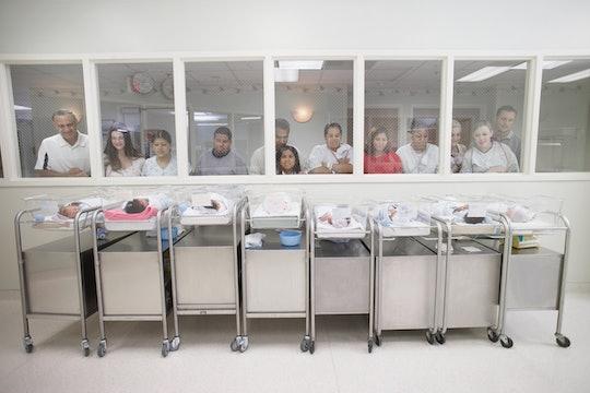 parents peer in at babies in a hospital nursery