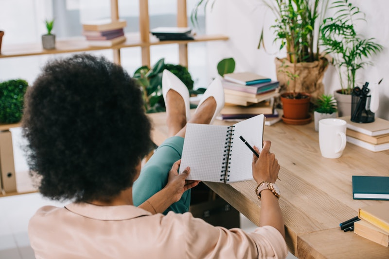 A person wearing white heels sits with her on her desk, poised to start writing in a notebook. Setting goals can be scary, but these weird hacks for achieving your dreams can help.