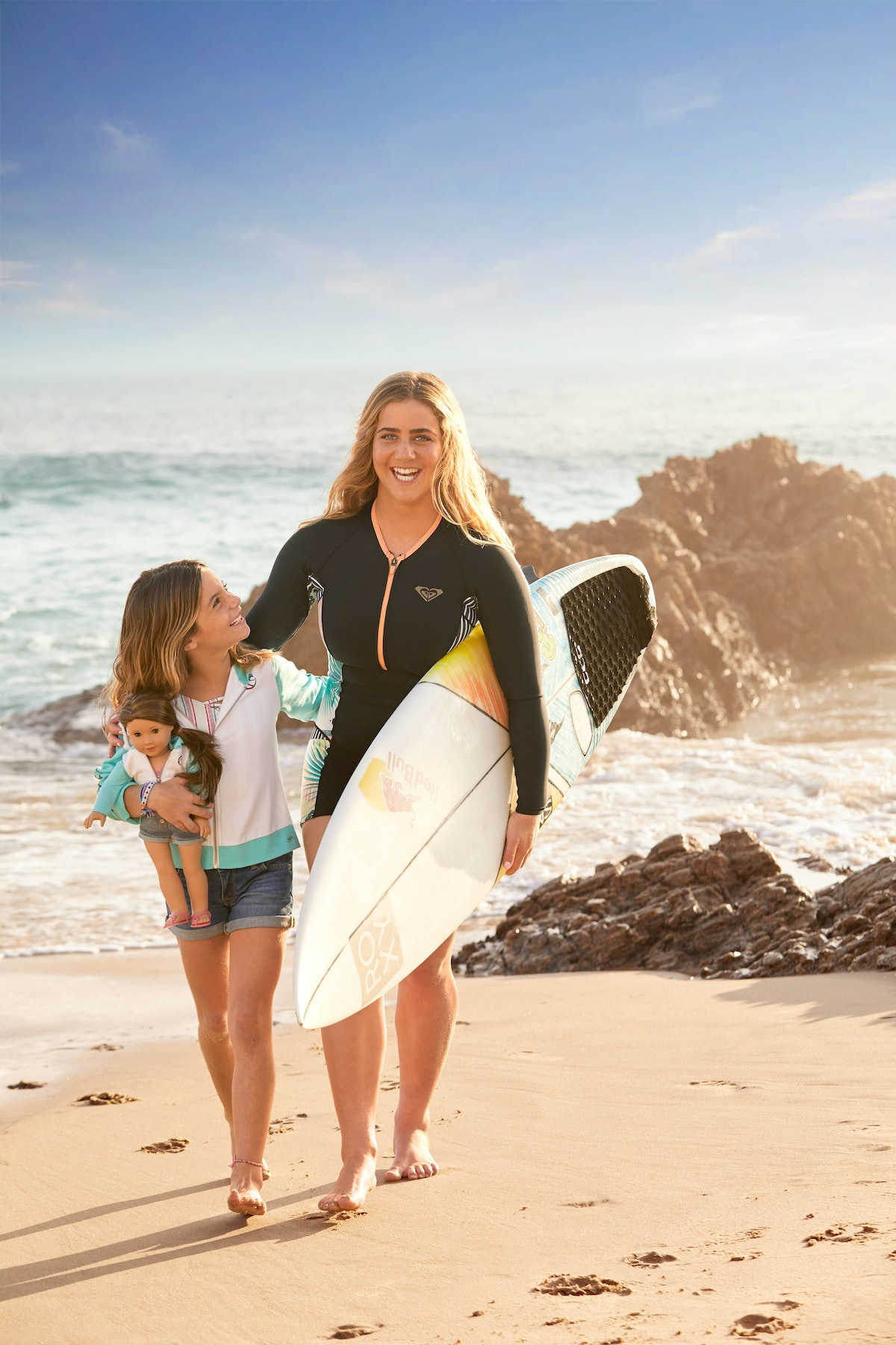 Olympic surfer Caroline Marks and sister walk on the beach with American Girl doll Joss Kendrick and a surfboard