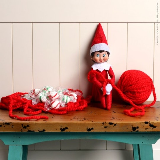 Elf on the shelf sitting on a bench tied up in red yarn with the ball of yarn sitting next to him.
