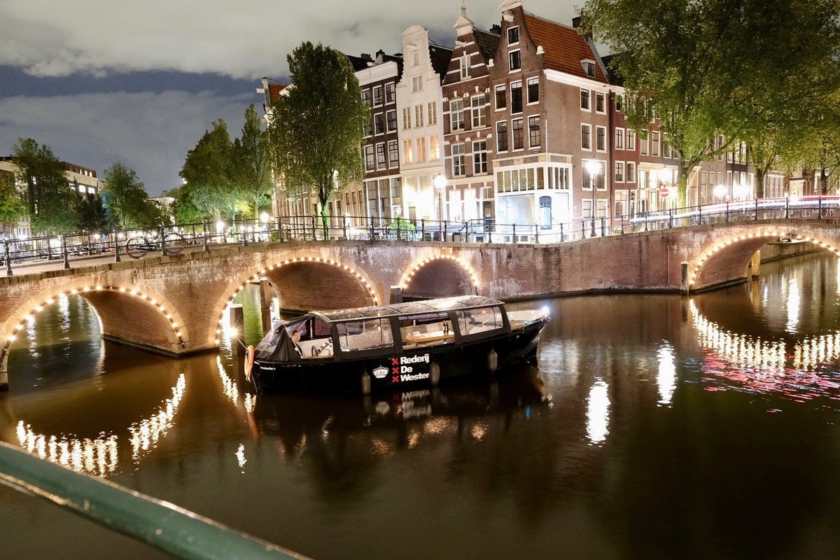 A canal boat rides through the Amsterdam canals during the winter with lights in the background.