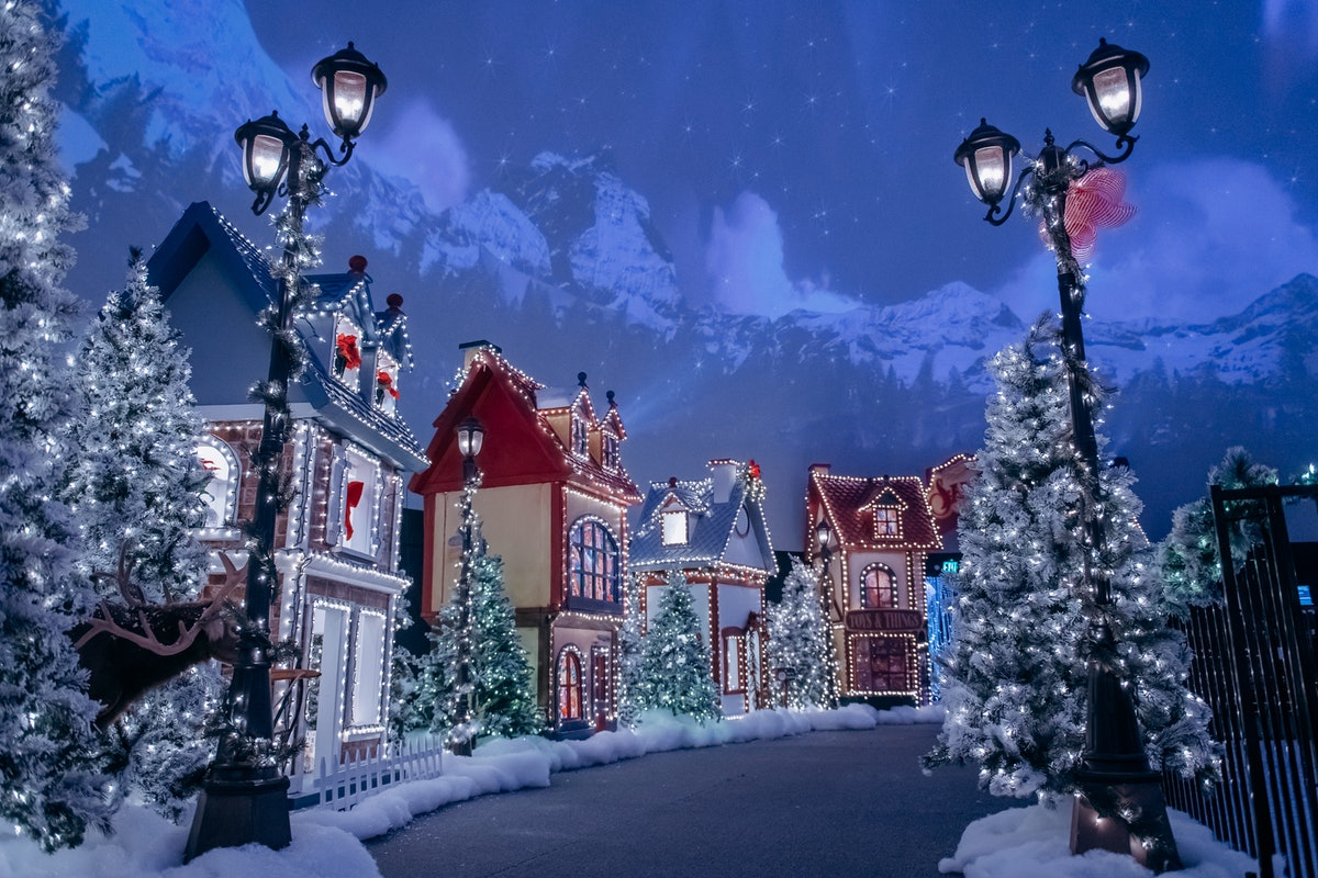 The Santa North Pole Village in LA has life-size elf houses, fake snow, and Christmas trees lit up with Christmas lights.