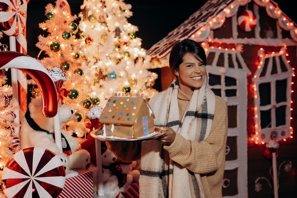 A woman smiles and holds up a gingerbread house at Santa's North Pole Village in LA.