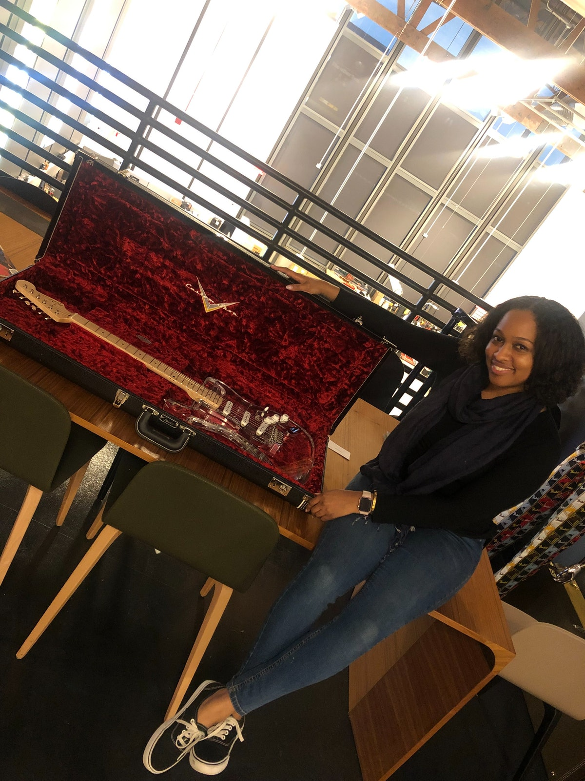 Moya Nkruma poses with a custom-made clear stratocaster guitar from Fender