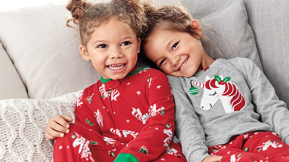 two little girls wearing holiday pajamas from Carter's