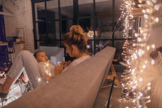 a mom holds a newborn by a christmas tree