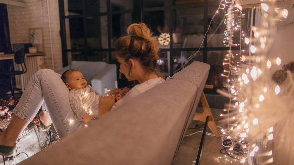 a mom holds a newborn by a christmas tree