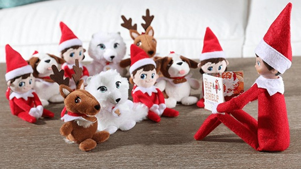 Elf on the Shelf reading a mini version of the 'Elf on the Shelf' book to mini stuffed animals