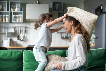 mom playing with daughter on couch