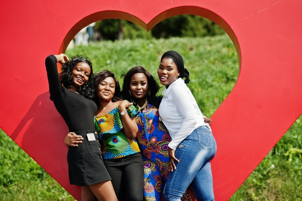 A group of women pose in front of a heart-shaped art installation outside on a sunny day.