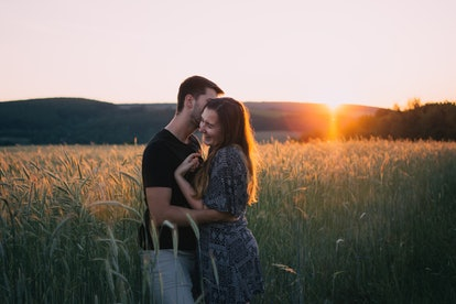 A happy couple embraces in a field at sunset.