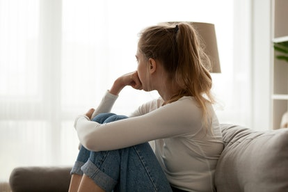 A young woman stares pensively out the window. Young women who are subjected to virginity tests are often left with a lower feeling of self worth.