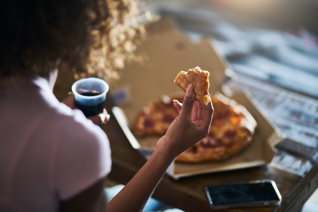 A person is eating pizza, while holding soda in their other hand. Pizza is a classic comfort food for Anna during a flare.