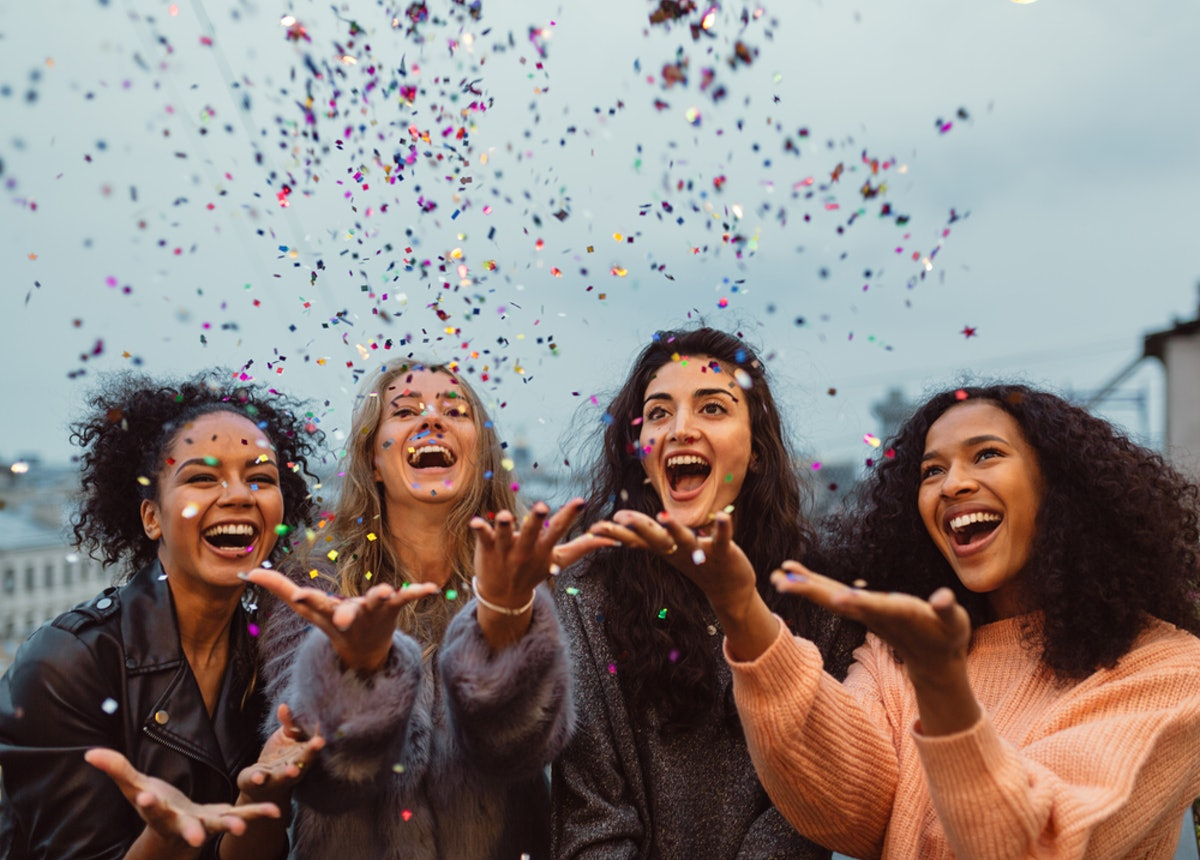 A group of four girls laugh and throw confetti in the air on a rooftop on New Year's Eve.
