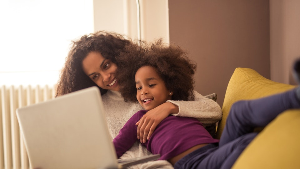 A mom on the computer, holding her daughter and laughing.