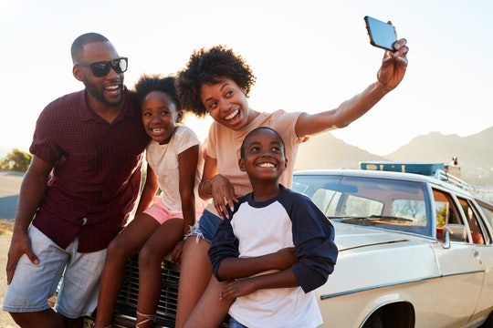 A happy family takes a selfie while sitting on the hood of their car in the summer.
