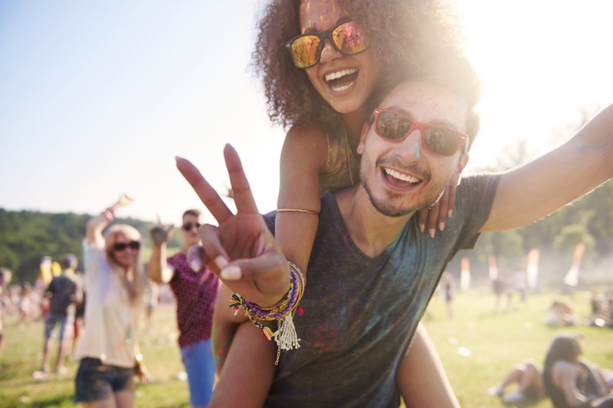A guy gives his girlfriend a piggyback ride while she makes a peace sign at a festival.