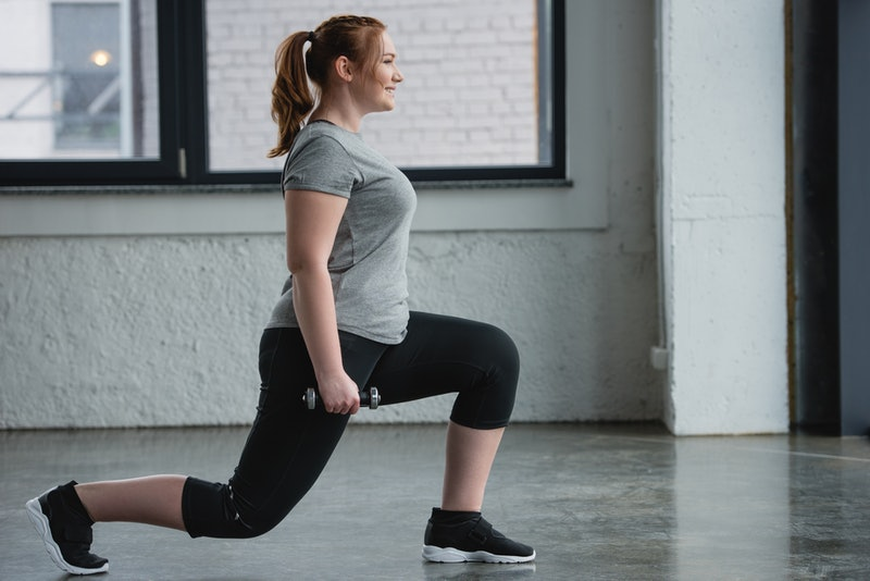 A person with a ponytail and grey t-shirt smiles while performing walking lunges in the gym. Walking lunges help with overall coordination, balance, and full-body strength.