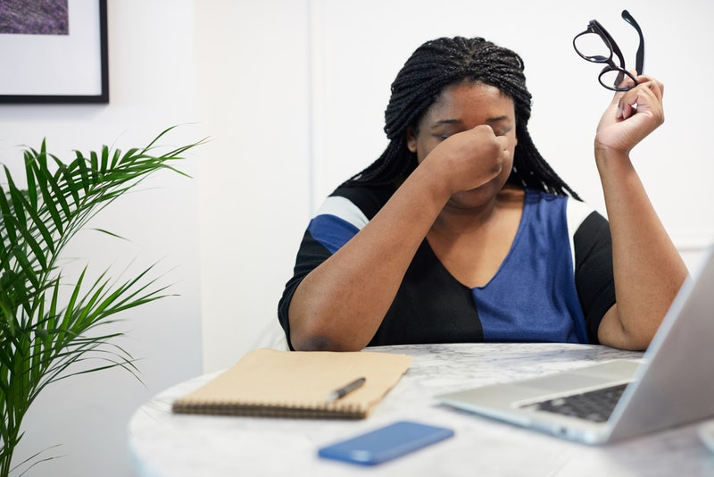 A stressed out person rubs the bridge of her nose with her glasses off. Experts reveal ways stress can physically change your brain.