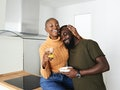 Couple cuddles in their kitchen after baby talking.