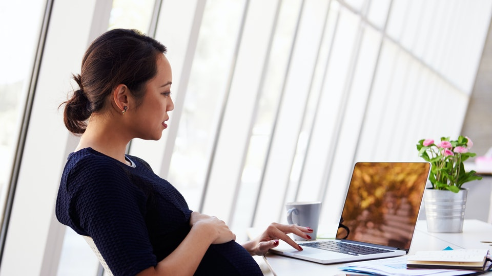 pregnant woman sitting at desk working on laptop