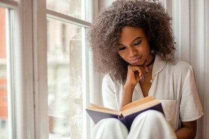A woman reads a book while sitting next to a window in her pajamas.