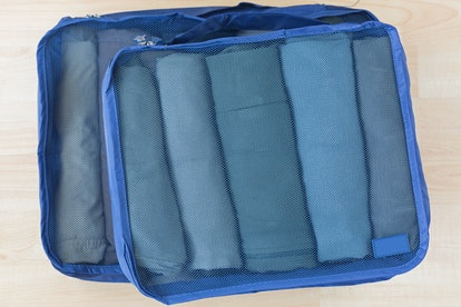Packing cubes can help you pack light when it is winter.