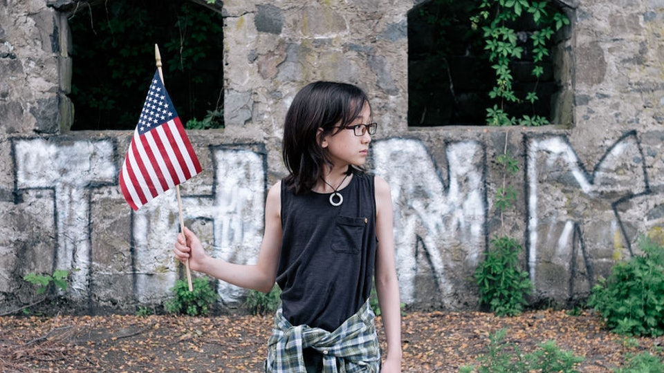 a young girl holding an american flag