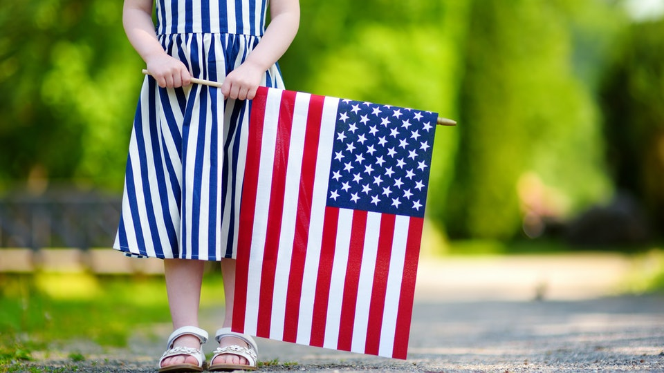 a little girl standing with an american flag
