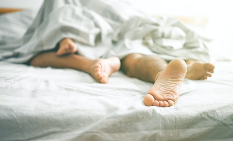 Couple in bed underneath the sheets, feet entangled