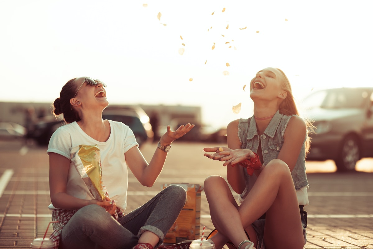 Two best friends smile while they sit on the ground and toss chips in the air at sunset.
