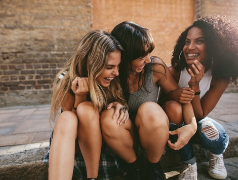 Three girlfriends laugh while sitting on a sidewalk.