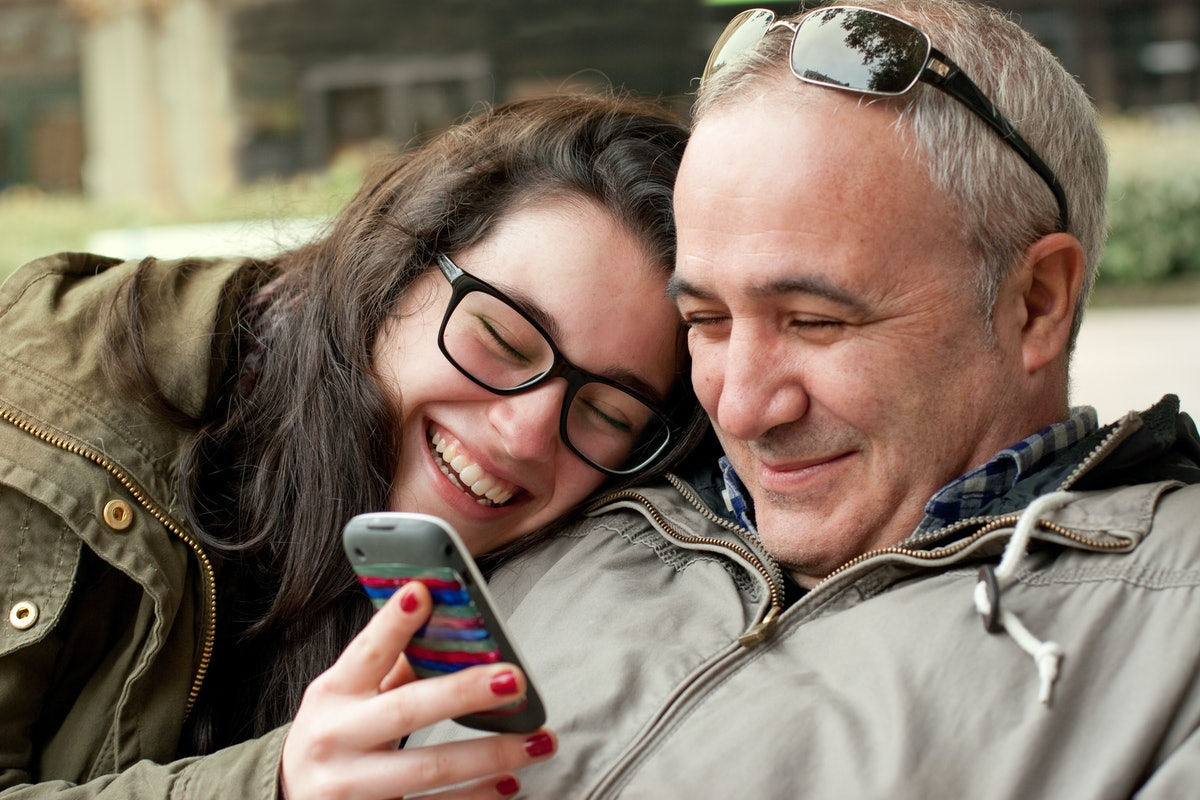 A father and daughter smile while looking at a cellphone.