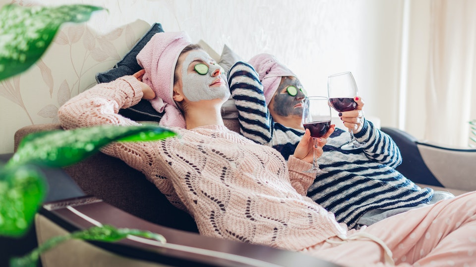 A mother and her daughter relax on a couch while holding wine glasses and wearing face masks.
