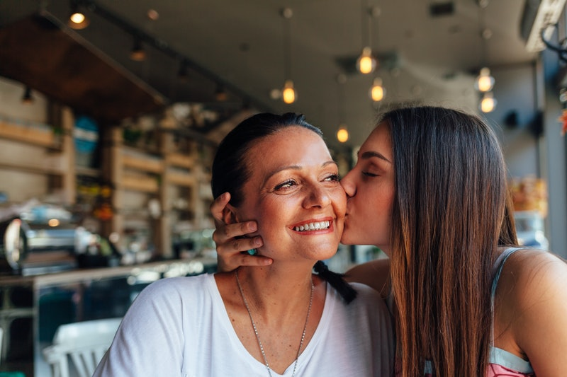 An adult daughter kisses her mom on the cheek while enjoying a meal at a restaurant.